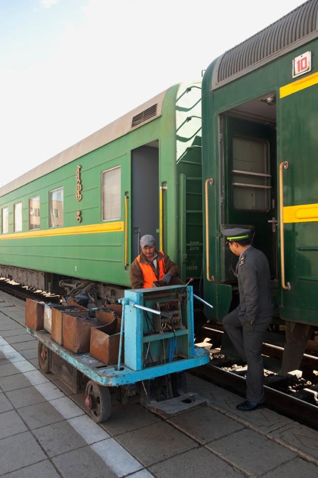 工作人員推著煤炭為車廂的煤爐加煤