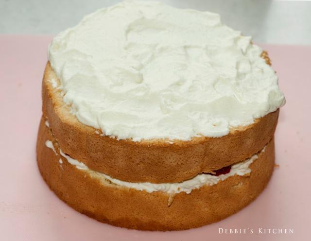 5. 疊上另一片蛋糕,用手輕輕壓實,在上面和側面抹上滿滿的鮮忌廉,然後抹至平順。