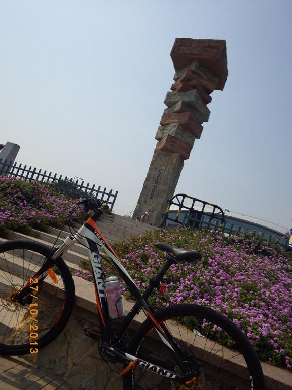 大運會火炬塔紀念廣場-火炬塔高26米,像一座書山,一本本叠起来的書上分别刻有各届大運會舉辦的時間和地點